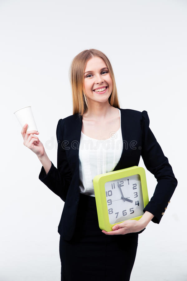 Busiensswoman holding cup of coffee and big clock. Smiling busiensswoman holding cup of coffee and big clock over gray background and looking at camera royalty free stock image