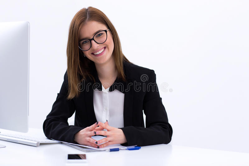 Busiensswoman sitting at her workplace in office. Portrait of a cheerful busiensswoman sitting at her workplace in office royalty free stock image