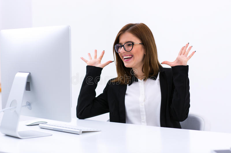 Busiensswoman sitting at her workplace in office. Portrait of a happy busiensswoman sitting at her workplace in office royalty free stock images