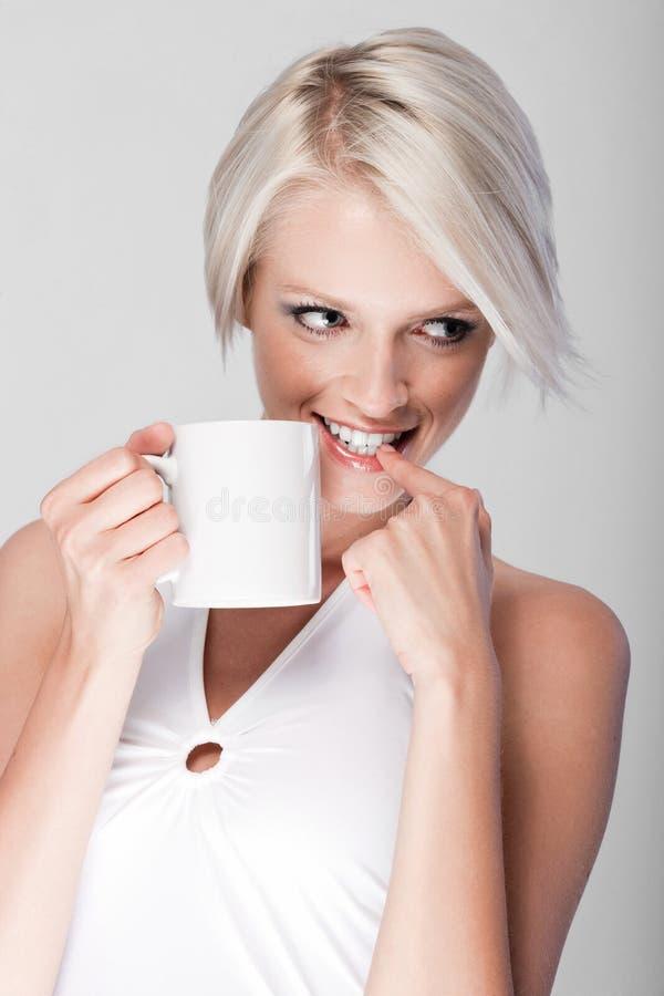 Busig ung kvinna som dricker kaffe royaltyfri foto