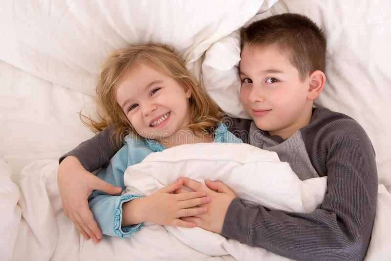 Busig ung syskongrupp i säng royaltyfria bilder