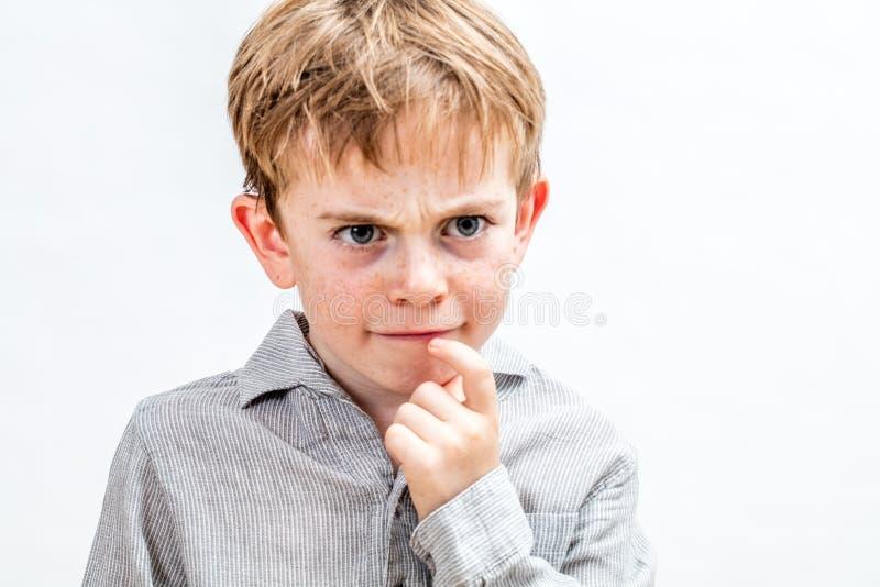 Busig unge med att rynka pannan fräknar som har tvivel för allvarlig lösning royaltyfria foton
