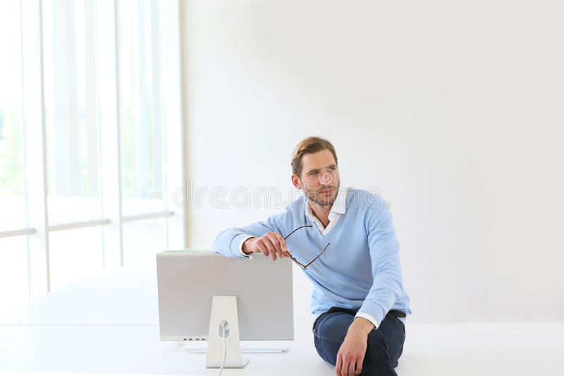Busineesman che si siede sullo scrittorio che si appoggia monitor fotografia stock libera da diritti