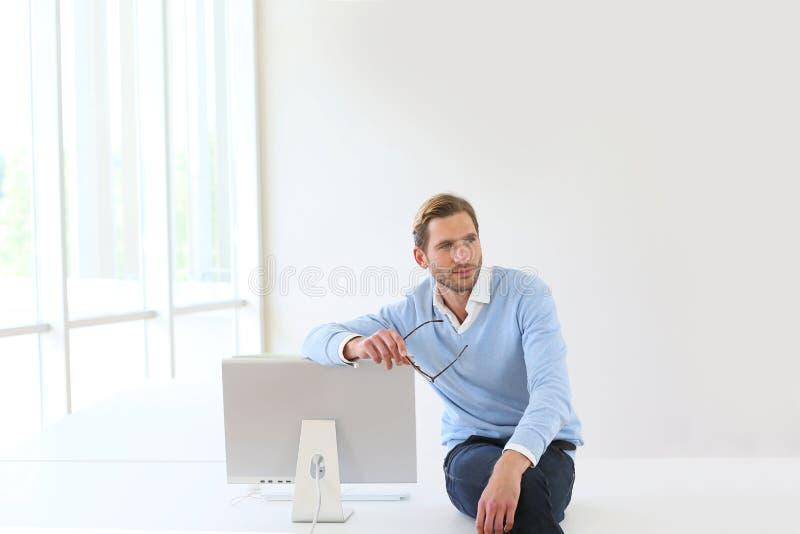 Busineesman, das auf dem Schreibtisch sich lehnt auf Monitor sitzt lizenzfreies stockfoto