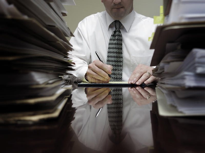 Businesman at Desk with Piles of Files and Papers royalty free stock photos