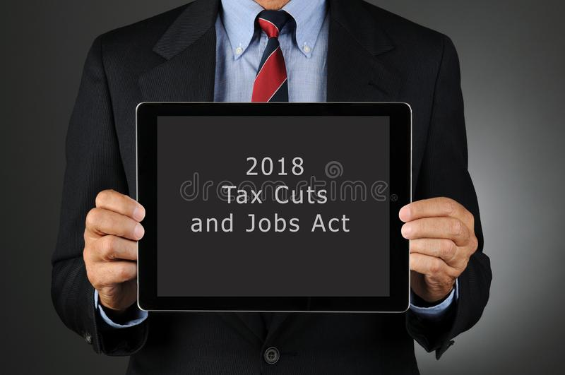 Businesman Holding Tablet with 2018 Tax Cuts and Jobs Act royalty free stock photo
