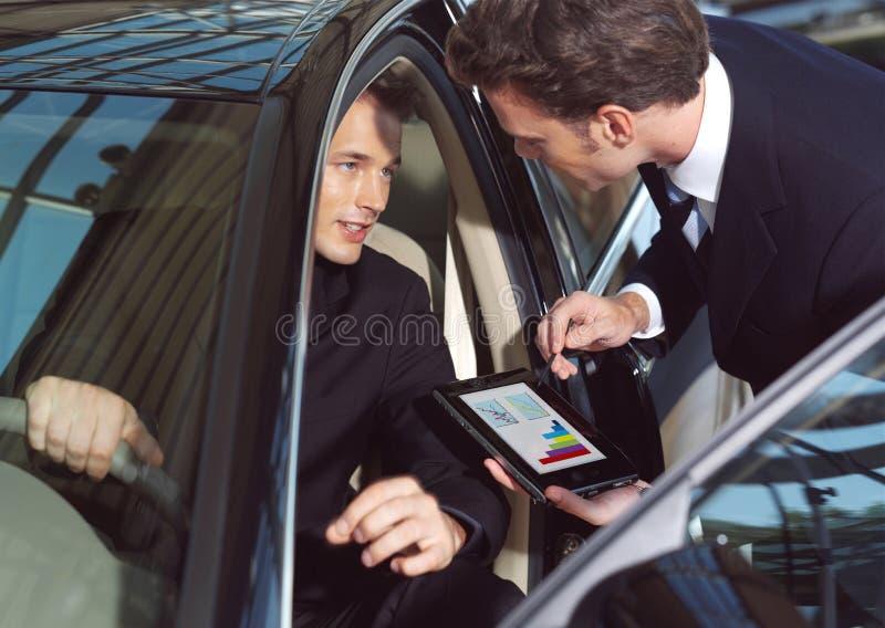 Businesmen working inside a car stock photo