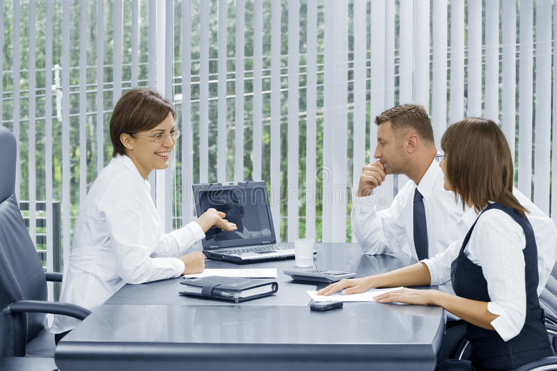 Business. Portrait of young business people discussing project in office environment royalty free stock photography