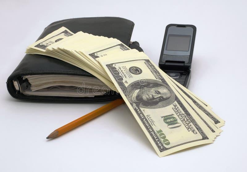 Business. Organaizer, mobilphone, pensil ad heap of dollars stock photo