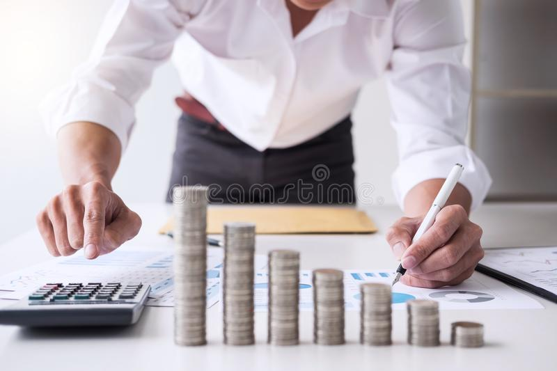 Business accountant or banker, businessman calculate and analysis with stock financial indices and putting growth stacking coin. And financial costs wisely and royalty free stock photos