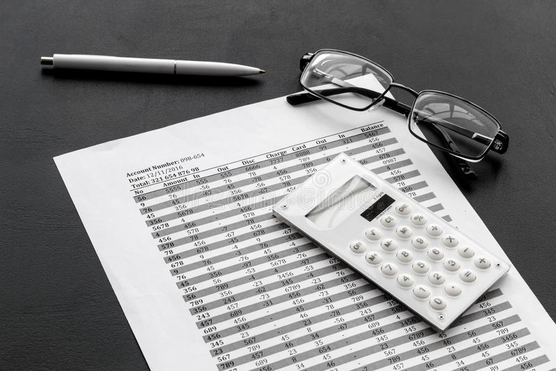 Business accounter work with taxes calculation and glasses on black office desk background stock photo