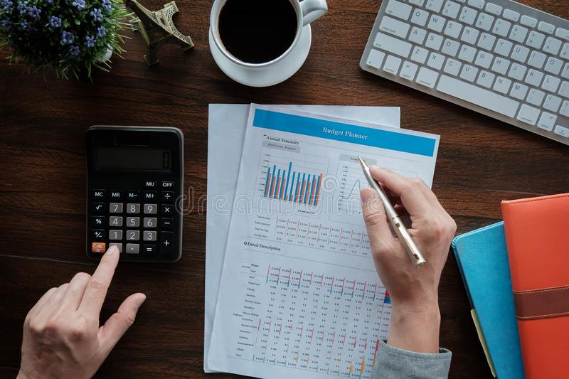 Business accounting concept, Business man using pen pointing  with data budget planner chart and calculator for calculate royalty free stock images