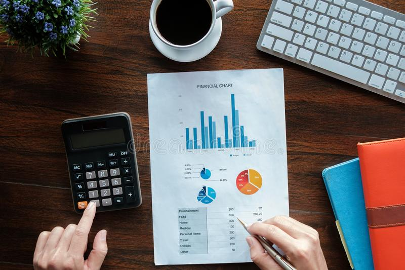 Business accounting concept, Business man using pen pointing  with stock maket data financial chart and calculator for calculate royalty free stock photos