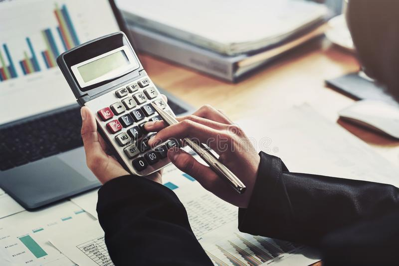 business accounting finance concept. accountant using calculator for calculate  with laptop working in office stock photography