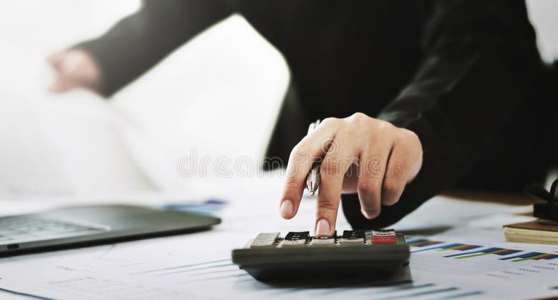 business accounting finance concept. accountant using calculator for calculate  with laptop working in office royalty free stock photo