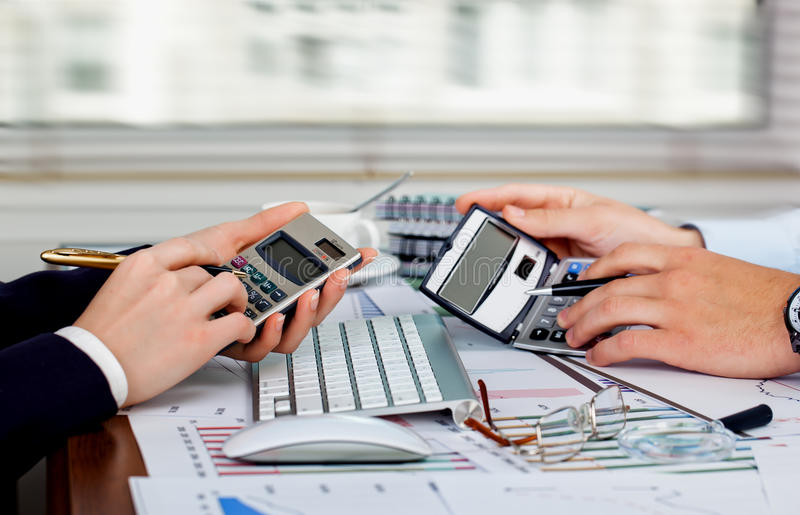 Business accounting. Hands with items for business in the office on the background of the diagram stock photo