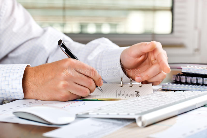 Business accounting. Male hand with things to do business in the office of the composition on the table stock photo
