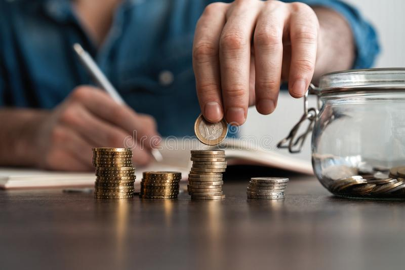 Business accounting with saving money with hand putting coins in jug glass concept financial. stock photos