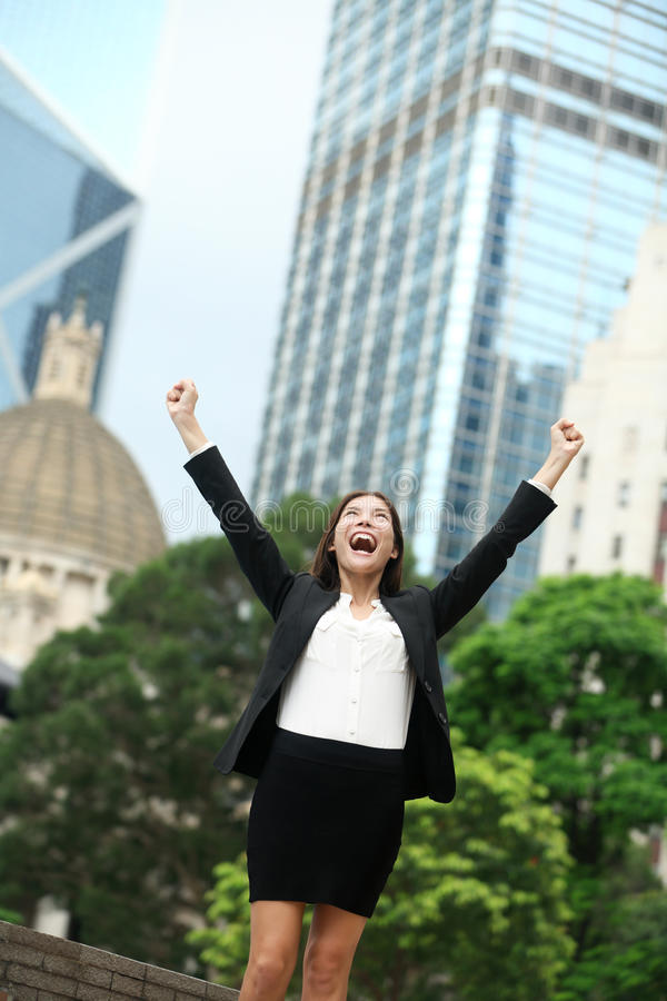 Business achievements success businesswoman. In Hong Kong celebrating business goals with arms raised up as winner. Young mixed race Chinese Asian / Caucasian royalty free stock photo