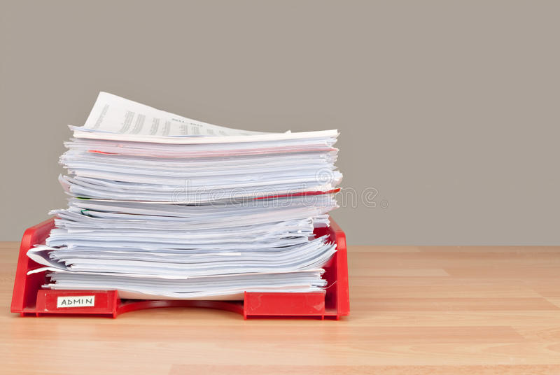 Business admin in-tray. Paperwork - lots of it - in red in-tray with handwritten label royalty free stock photo