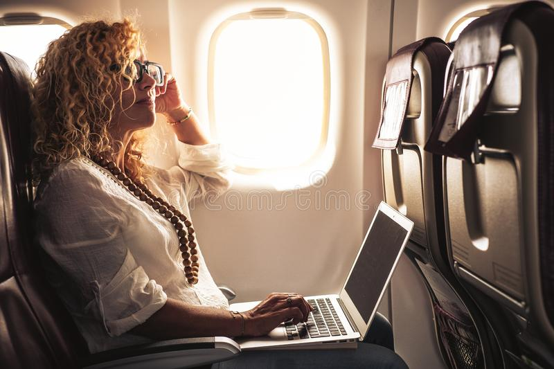 Business adult beautiful curly blonde woman travel on airplane connected to internet with modern computer laptop - people on work. Everywhere and digital nomad royalty free stock photography