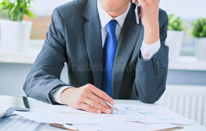 Business analysis concept. Businessman in black suit analyzing business documents, financial report, working on tablet stock images