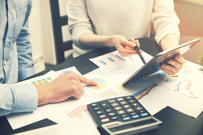 Business analysis - people discussing financial graphs at office stock photo