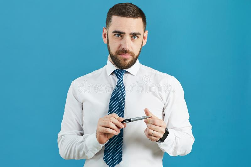 Business analyst twisting pen. Portrait of content handsome bearded business analyst in formal shirt standing against isolated background and twisting pen while royalty free stock photo