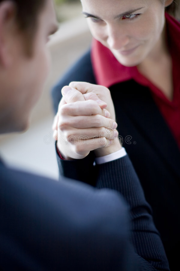 Business arm wrestle. Businessman and businesswoman wearing suits sit as they arm wrestle royalty free stock photography