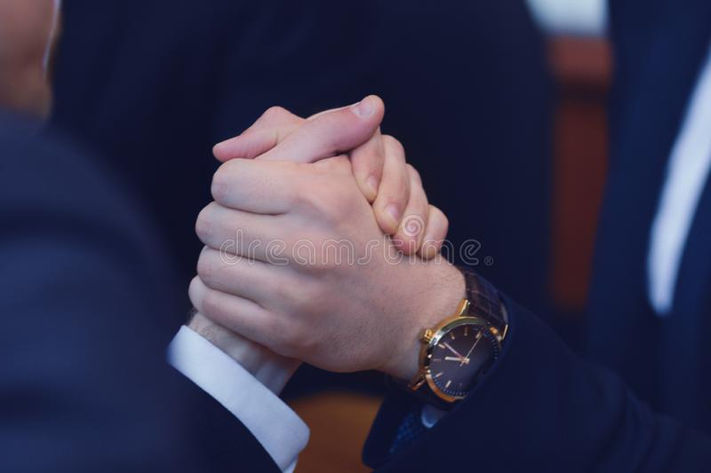 Business armwrestling in office. Male hands compete in armwrestling after signing agreement. Business power concept stock image
