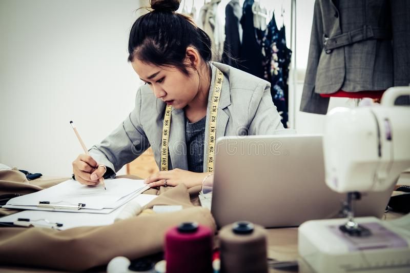 Business Asian fashion designer have no idea when designing new collection of dress in workshop studio. Dressmaker headache and. Negative thinking concept royalty free stock photo