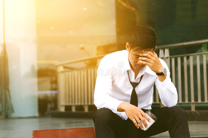 Business asian man sitting front company and stressed or worried royalty free stock images
