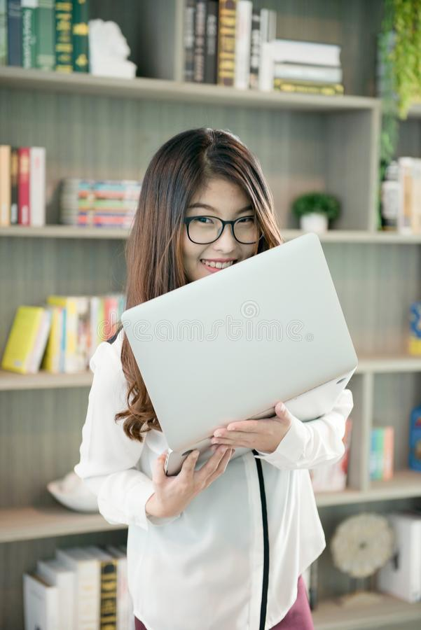 Business Asian woman holding a laptop in library stock images