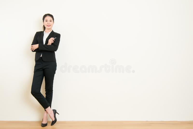 Business asian woman holding pen cross arm standing. In front of white wall with white wall background, great for your design or text, beautiful asian office stock image