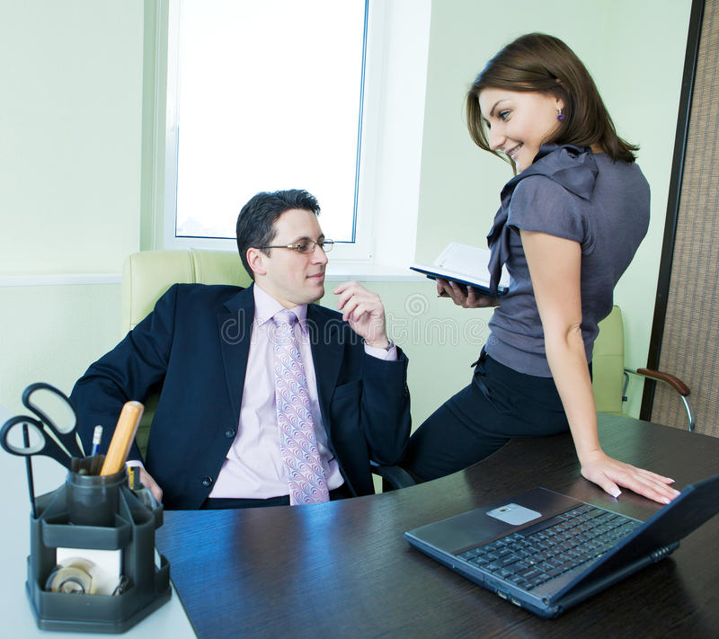 Business assistant flirting with boss. In office interior royalty free stock photo