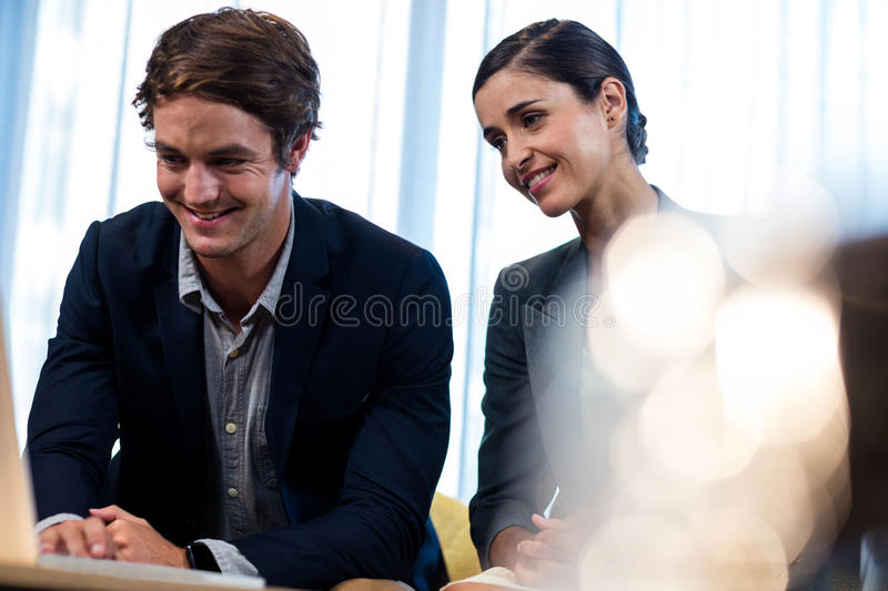 Business associate looking a laptop. In the office stock images