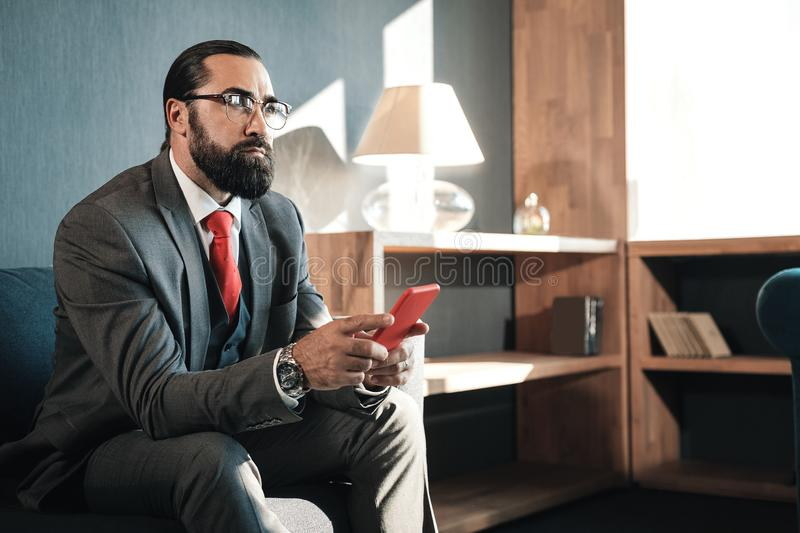 Bearded man wearing business attire feeling concerned before negotiation. Business attire. Bearded man wearing business attire feeling concerned before very stock photos