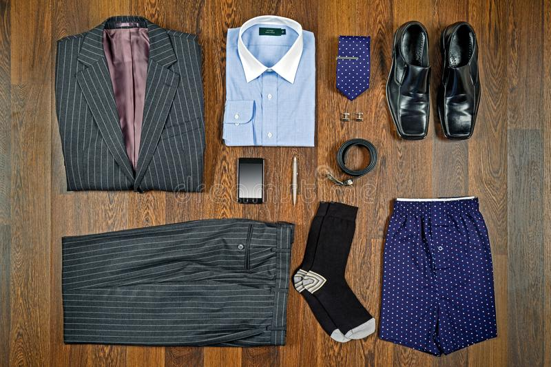Business attire flat lay. A flat lay arrangement of mens business attire with grey pin striped suit, white collar shirt, black shoes and matching accessories stock images