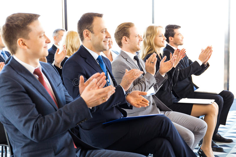 Business audience applaud at training. Audience of happy business people sitting at training room, conference hall, applauding to speaker stock photos