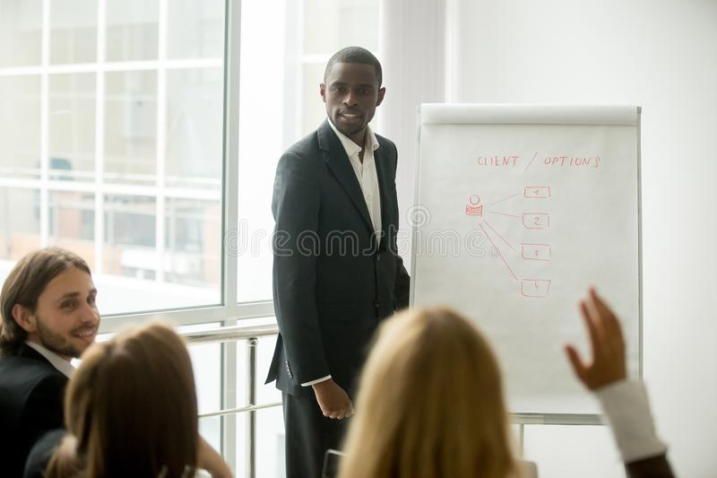 Business audience asking african presenter speaker questions at stock images