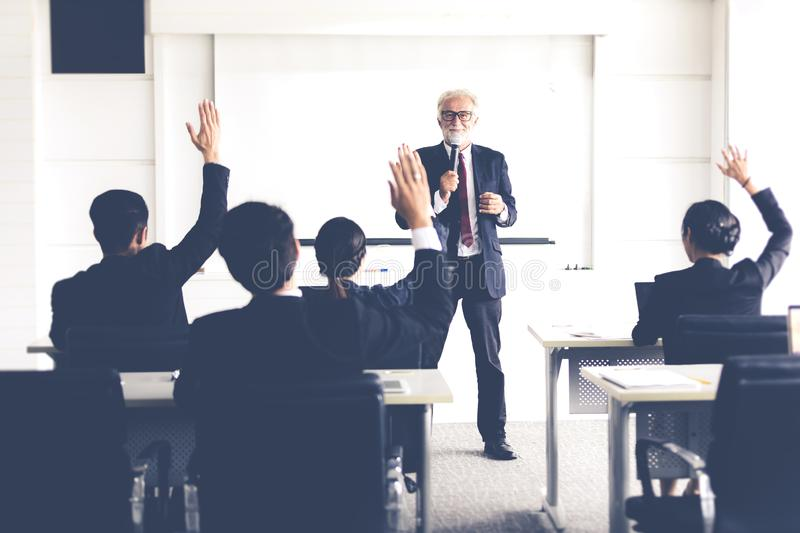 Business Audience raising hand up while businessman is speaking in training for Opinion with Meeting Leader in Conference Room.  royalty free stock image