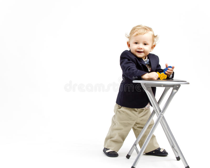 Business baby. Laughing office baby dressed in business outfit next to a small chair stock images
