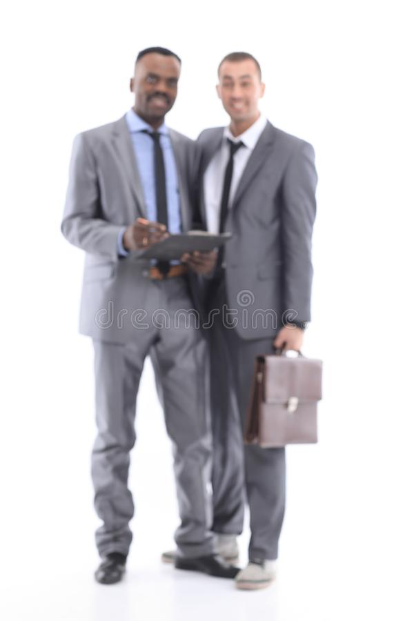 Business Background Blur Concept. Blurred image of two young employees working together on a white background stock photography