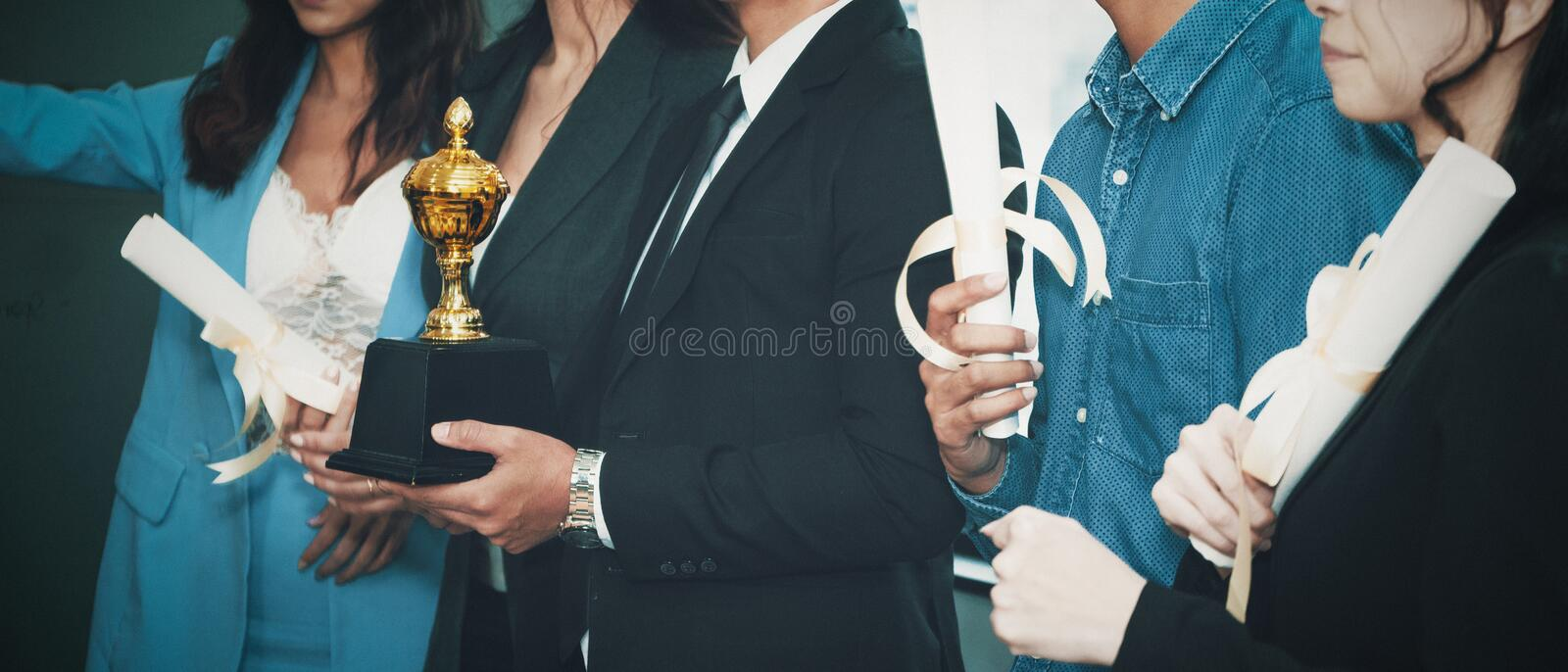 Business background of business people standing tohetger with trophy and certificate awards on hand.  royalty free stock photo