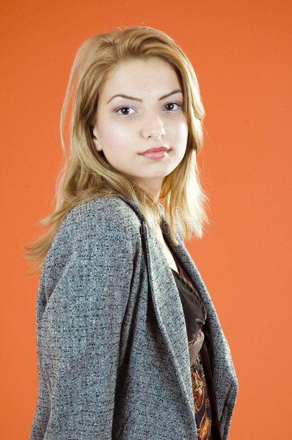 Business Beauty. Portrait of a young blond woman in business wear. Shot in studio with an orange background stock photos