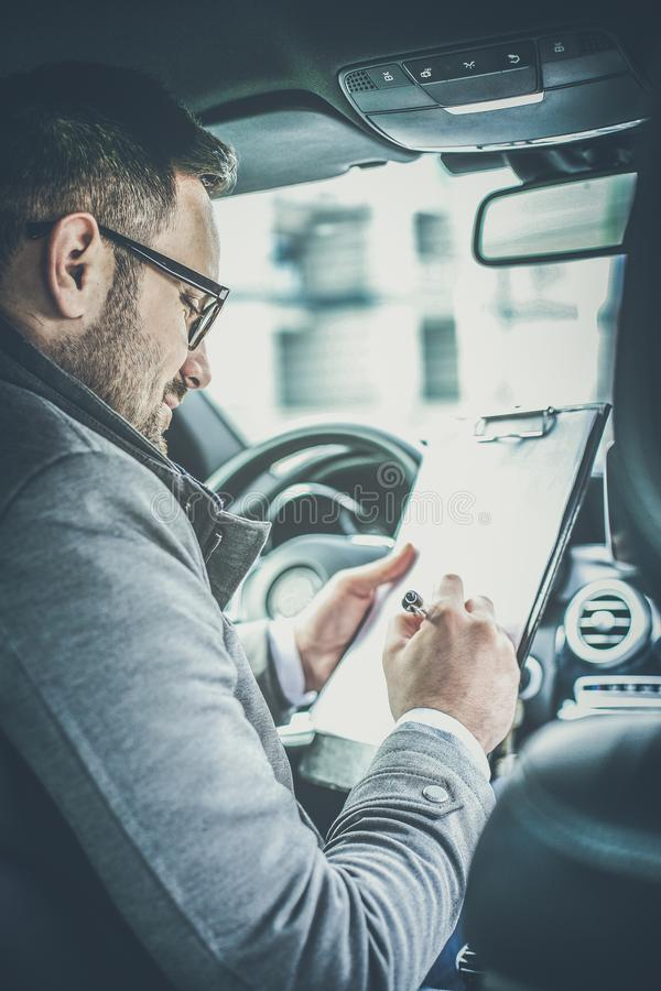 Business begins before he steps into the office. Business man sitting in car and writing on document. Close up royalty free stock images