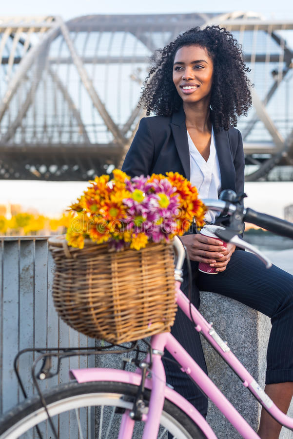 Business black woman with vintage bicycle drinking coffe royalty free stock photography
