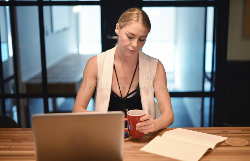 Business blonde girl drinking a cup of coffee in front of a laptop royalty free stock images