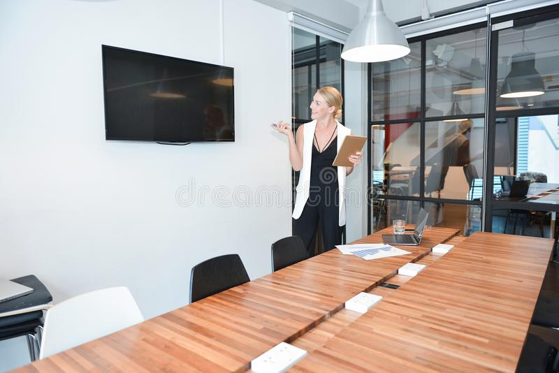 Business blonde woman presenting a project on blank screen TV stock photography