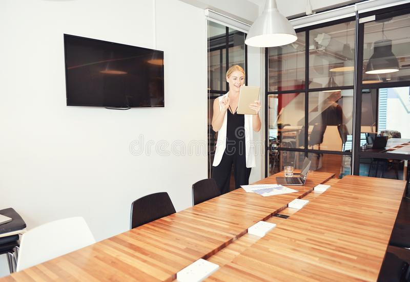 Business blonde woman presenting a project on blank screen TV royalty free stock image